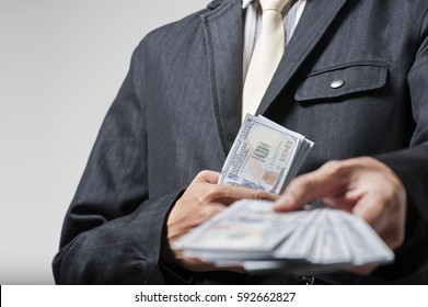Business man giving bank notes to another person