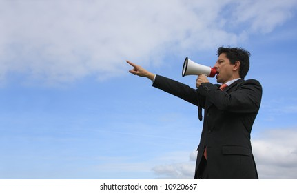 A business man giving an order with a megaphone with a blue sky as Background