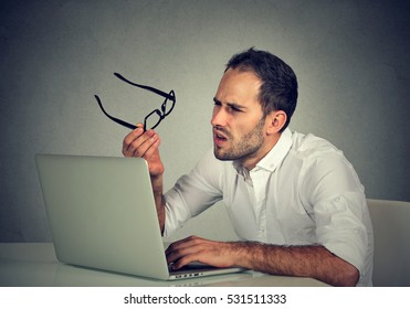 Business man with glasses having eyesight problems confused with laptop isolated on gray background. Vision related changes. Human face expression