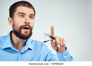 business man with glasses in his hand shows his finger to the side on a light background