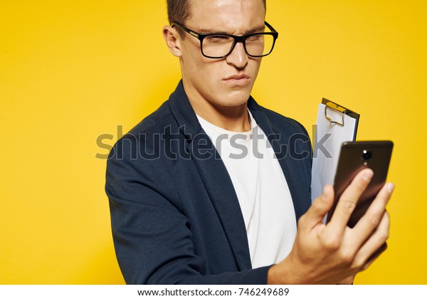 business man in glasses with phone on yellow background portrait