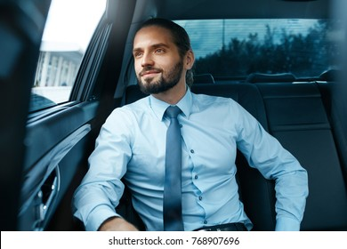 Business Man Going To Work In Car. Portrait Of Handsome Successful Young Businessman In Formal Wear Traveling On Back Seat Of Vehicle And Looking Through Window. Business Travel. High Quality Image.
