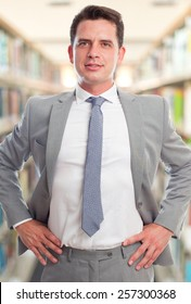 Business man with grey suit. He is looking confident. Over library background
