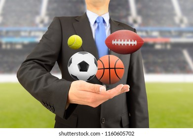 Business man with group of balls of different sports in hand at stadium