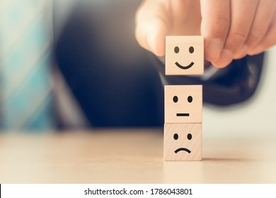 business man hand arranging  wooden block cube and choose smiley face icon, customer service satisfaction concept