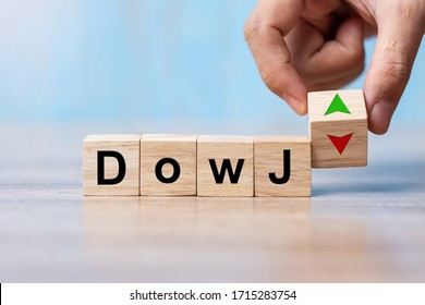 business man Hand change wood cube block with Dow J text to UP and Down arrow symbol icon. Interest rate, stocks, financial, ranking, mortgage rates and Cut loss concept