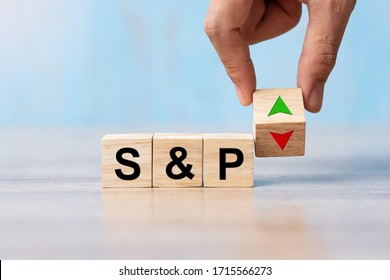 business man Hand change wood cube block with S&P text to UP and Down arrow symbol icon. Interest rate, stocks, financial, ranking, mortgage rates and Cut loss concept