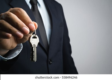 business man hand giving keys on white background on white background
