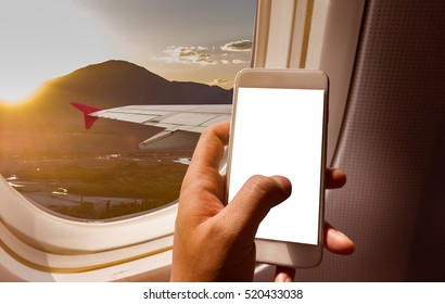 business man hand holding blank screen smart-phone on board of airplane near window seat and wing with Himalayas mountain range