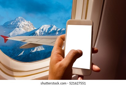 business man hand holding blank screen smart-phone on board of airplane near window seat and wing with Alps mountain range
