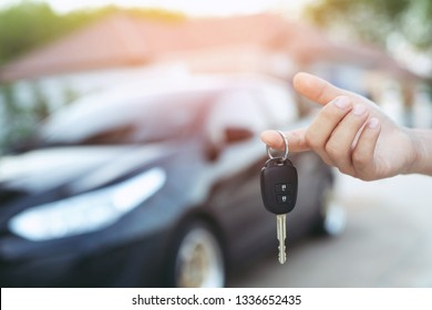 Business man hand holding car keys front with car on background. parking in front of the house. transportation concept