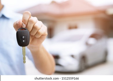Business man hand holding car keys front with new car on background. parking in front of the house. transportation concept. Leave copy space to write messages text.