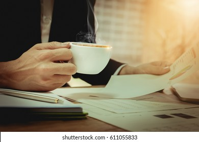 Business man hand holding coffee hot cup with use laptop computer  and notebook doing finance at home office.