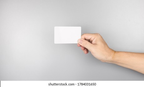 Business man hand holding credit card isolated on white background. 					Plastic name card mock up show template display front design.  					Credit card instead of cash payment concept.
