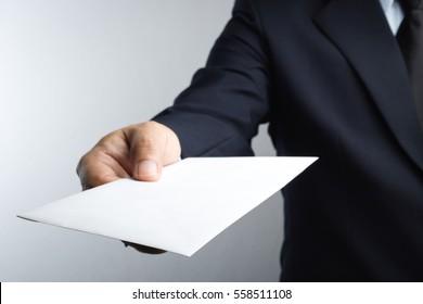 Business man hand holding envelope on white background