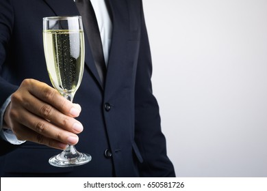 Business man hand holding glass of champagne for celebration on white background