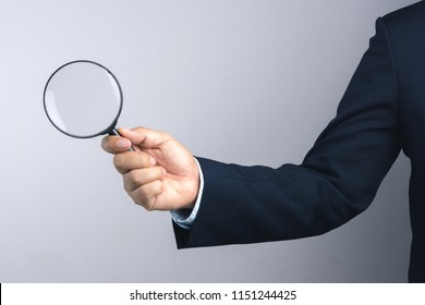 Business man hand holding magnifier for inspection on white background