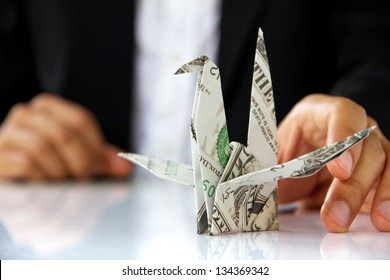 business man hand holding origami paper cranes, money concept