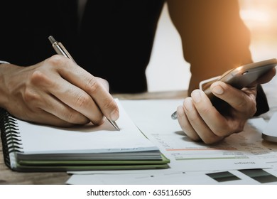 Business man hand holding pen point notebook and use smartphone doing finance at home office.