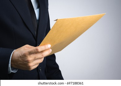 Business man hand holding a self sealing brown envelope document on white background