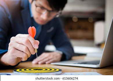 Business Man hand holding a target with darts hitting the center