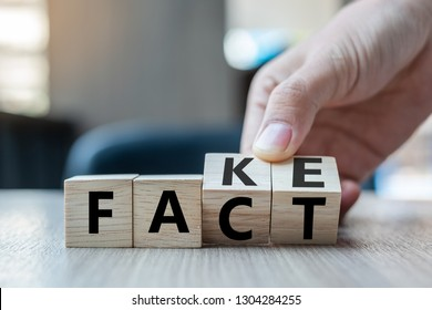 Business man hand holding wooden cube with flip over block FAKE to FACT word on table background. News, solution and business  concepts