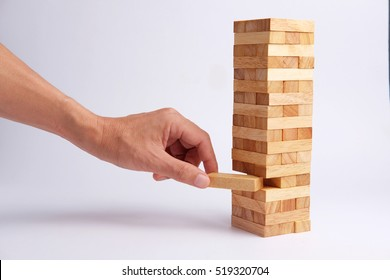 Business man hand pick and put of wooden block tower in shape on gray background. Selective focus and blank space. Business concept for process teamwork and growth success process.