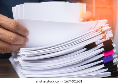 Business man hand pick up Stack overload document report paper with colorful paperclip, business and paperless concept.