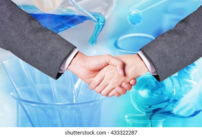 business man hand shake with chemistry research at science lab blur background