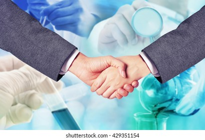 business man hand shake with medicine research at science lab blur background