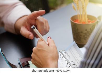 Business man hand show objection gesture.Conversation at business lunch meeting in cafe outdoors.Female hand writing in paper notebook.Gesturing businessman.Male hand pointing with finger on woman