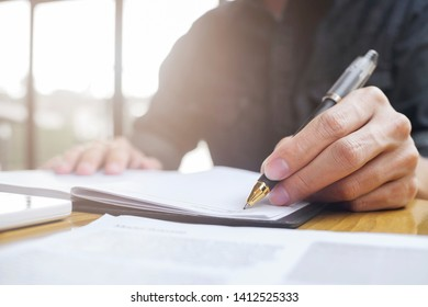 business man hand signs a documents at office.
