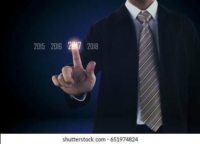 Business man hand touching on virtual screen. pointing to year 2017