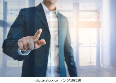 business man hand touching screen with office background