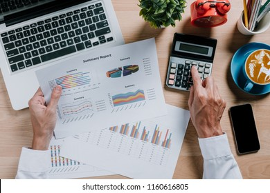 Business man hand working with financial data and calculator  on wihite desk in modern office.Business analysis and strategy concept.