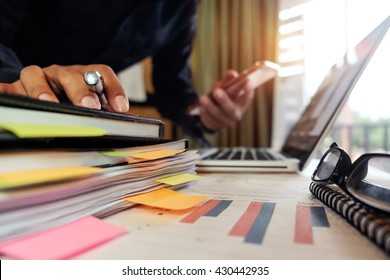 business man hand working on laptop computer and holding smartphone with  business graph information diagram and stack of books on desk as concept in morning light