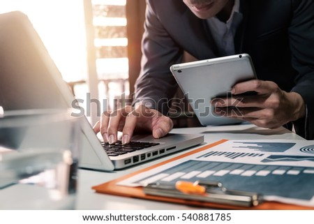 business man hand working on laptop computer and holding tablet with digital layer graph information diagram on desk as concept in morning light
