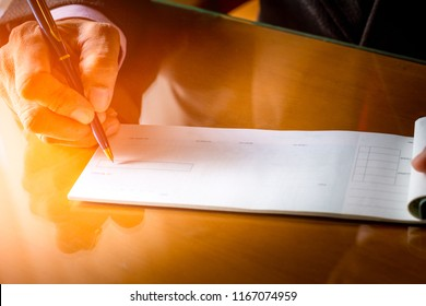 Business man hand writing and signing checkbook on the wooden table background at office. Paycheck or payment by cheque concept.