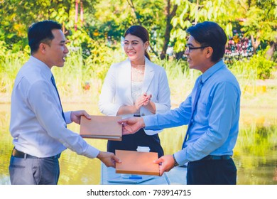 Business man handing a contract agreement and after a deal between business success.  Business women clapping nice and smile .They are happy beside stream in park. Photo concept  business and succeed.
