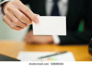 business man is handing white card , paper