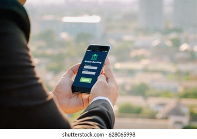 business man hands hold mobile banking on smart phone on blurred urban city as background