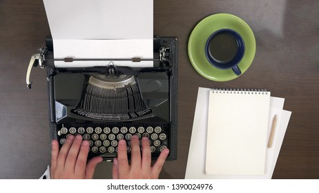 Business man  hands typing at vintage typewriter, take a cup of coffee