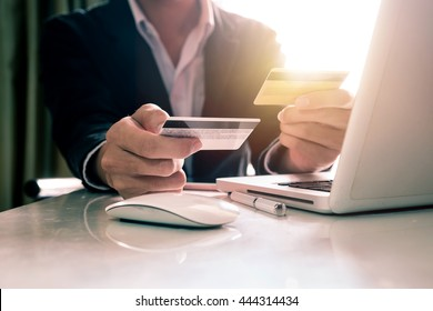 Business man hands using laptop and holding credit card with digital layer effect diagram as Online shopping concept