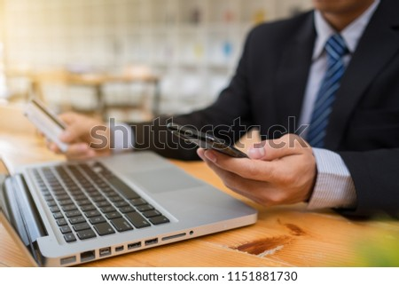 Business man hands using laptop and holding credit card and smart phone with digital layer effect diagram as Online shopping concept