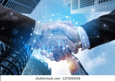 business man handshake with global network link connection, graph chart of stock market graphic diagram and city background, digital technology, internet communication, teamwork, partnership concept