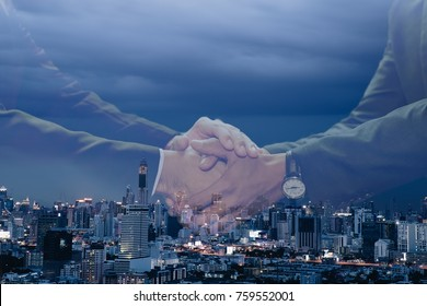 Business man handshake on night scene of city background. Double exposure effect. Use for business or background concept.