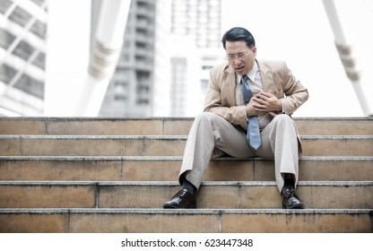 Business man having heart attack or heart failure at the steps in front of his office building