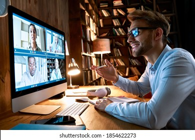 Business man having virtual team meeting on video conference call using computer. Social distance worker working from home office talking to diverse colleagues in remote videoconference online chat.