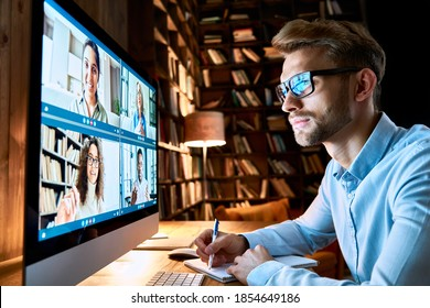 Business man having virtual team meeting on video conference call using computer. Social distance employee working from home office talking to diverse colleagues in remote videoconference online chat.