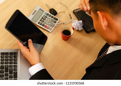 Business man headache with hand holding tablet on wood table desk